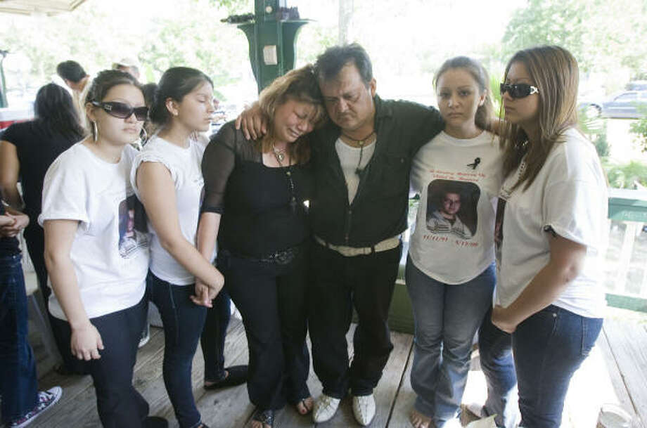 Vidal Herrera's parents, Evelia and Vidal Herrera, center, gather with his sisters, from left, Maricela, Karina, Marisa and Rosie after the funeral Saturday for the 17-year-old. Photo: James Nielsen, Chronicle