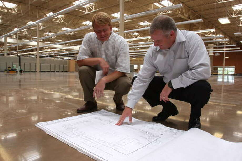A Kroger Marketplace is scheduled to open this fall at the Grand Parkway and Mason Road. Examining store blueprints are Regency Centers officials Erik Tompkins, left, property manager, and Steve Fritzer, vice president of investments. Photo: Suzanne Rehak, For The Chronicle
