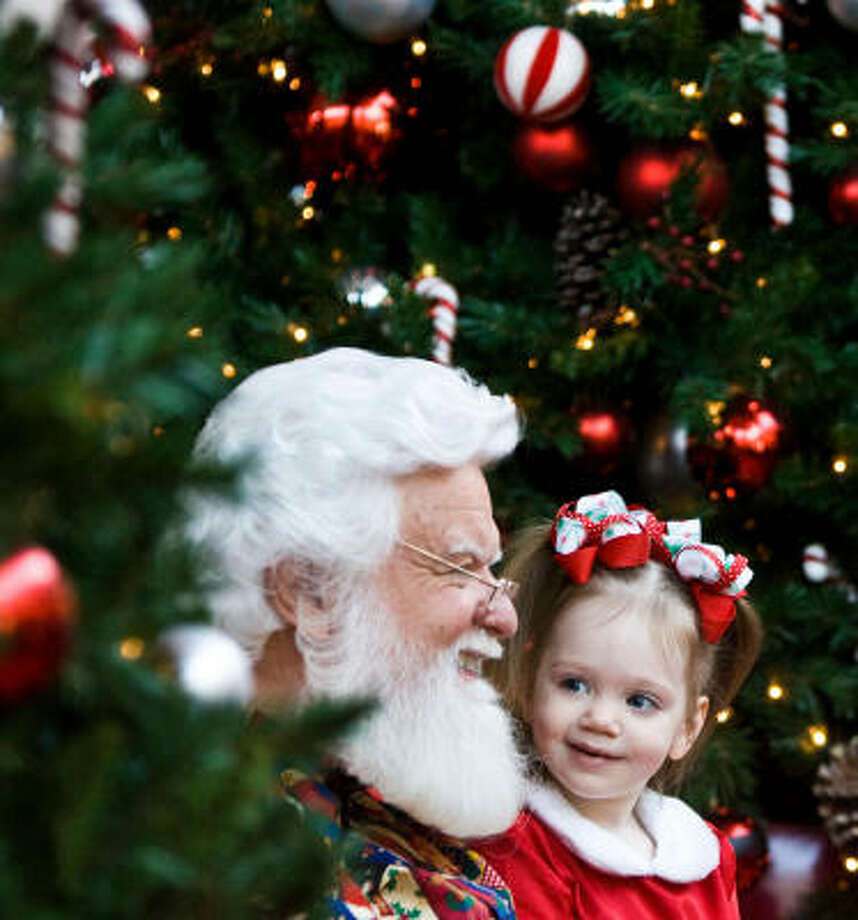 Julia Barber, 2, takes a close look at Santa's bushy white beard after visiting with him and posing for her Christmas picture Thursday at the Baybrook Mall in Friendswood. Photo: Nick De La Torre, Chronicle