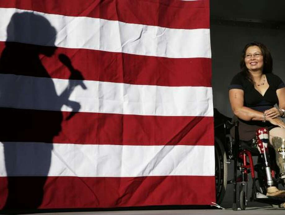 L. Tammy Duckworth, who lost her legs while deployed in Iraq in 2004, looks on as a silhouetted Michelle Obama addresses volunteers at the 2008 Democratic National Convention. Photo: JACK DEMPSEY, ASSOCIATED PRESS