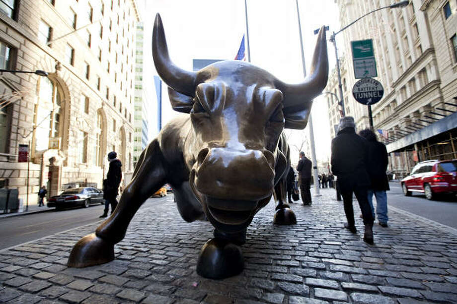 A bull statue sits near the New York Stock Exchange. The six largest U.S. banks are on track to hand out as much as $149 billion for bonuses and other compensation for 2009. Photo: Daniel Acker, Bloomberg