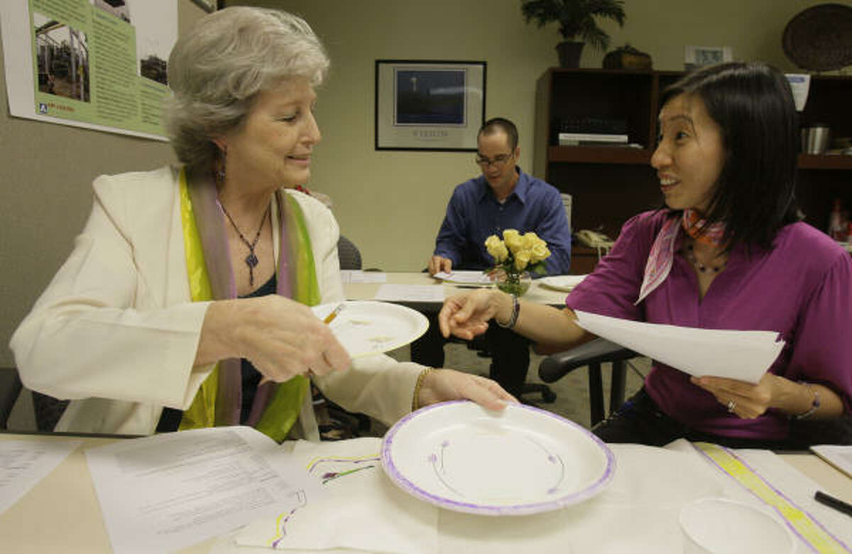 Employees Joan Rhodes, left, and Wendy Yip are role-playing ordering food in French.