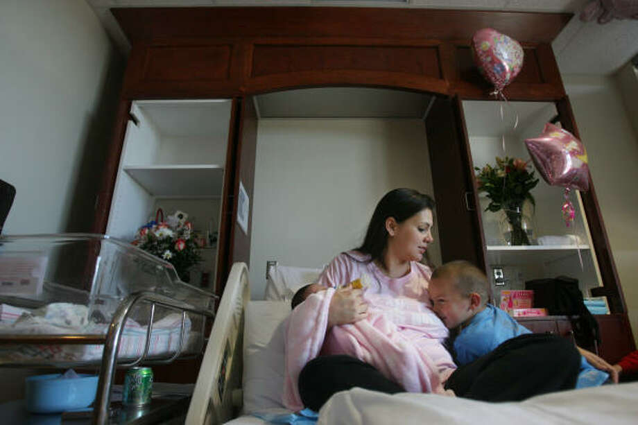 Angie Weesner plays with her newly expanded family, 2-day-old Aralyn Grace and new big brother Adrien, at her private room at The Methodist Hospital in Sugar Land on Feb. 5. Hospitals are adding amenities to maternity rooms to attract pregnant women. Photo: Mayra Beltran, Chronicle