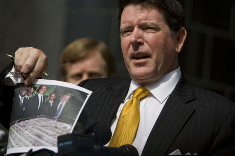 Dan Cogdell, attorney for Laura Pendergest-Holt, the chief investment officer of  Stanford Financial Group, holds a photo of other Stanford executives as he says his client is innocent during her arraignment on a criminal charges Friday. Photo: Sharon Steinmann, Chronicle