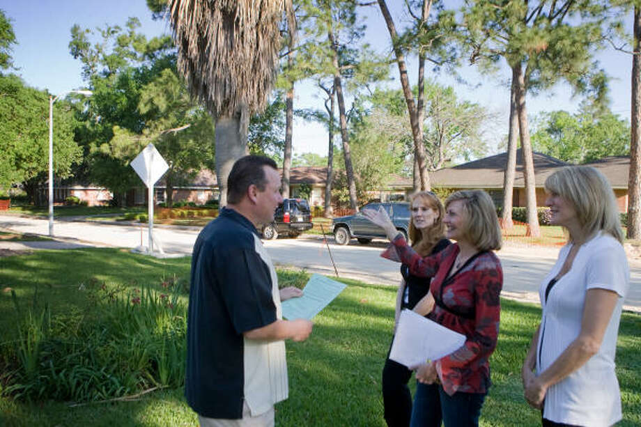 PITCHING IN: Mark Smith listens as Earlene Stewart, middle, Kara Bailiff, left, and Bobbi Nygaard drum up support for their efforts to improve street lighting in the Braeswood Place subdivision, north of Braeswood at Stella Link. Photo: R. Clayton McKee, For The Chronicle