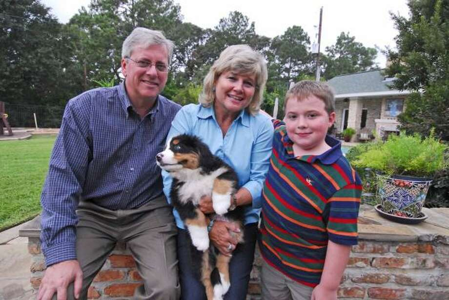 Steve Ward and Kris Ward with their 10-year-old son Jared Ward and their Bernese mountain dog puppy, Jackson. Photo: Tony Bullard, ALL