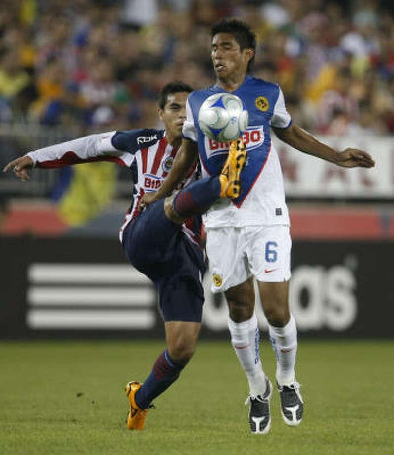 Club America's Juan Carlos Valenzuela, front, battles Chivas midfielder Xavier Baez for the ball in the second half. Photo: Julio Cortez, Chronicle