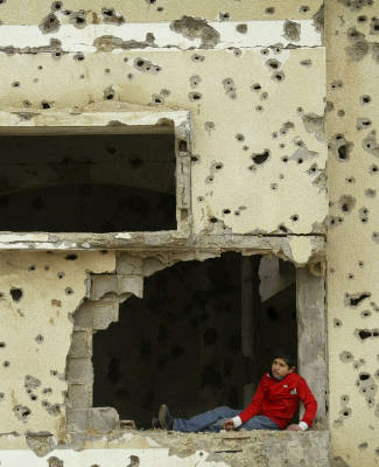 A Palestinian sits in the window of a bullet- and shrapnel-riddled house in Rafah, southern Gaza Strip, on Monday. The Palestinian president asked international donors at a conference Monday to funnel millions of dollars through his government to rebuild the devastated Gaza Strip. Photo: EYAD BABA, Associated Press