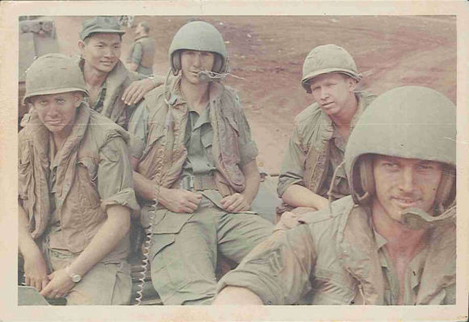 That's Capt. John Poindexter, center, a Vietnamese scout and interpreter leaning on his shoulder, and some of the armored cavalry assault vehicle crew. Photo: Courtesy Photo