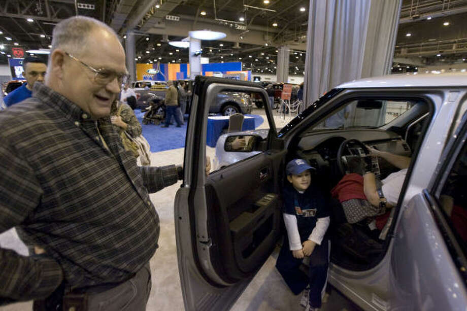 JOHNNY HANSON : CHRONICLE FLEXIBLE: Jim Rosser, left, from Corpus Christi, who was a former Ford employee in Detroit, looks at the interior of the new Ford Flex with his son Ryan, 7, Saturday at the Houston Auto Show at the Reliant Center in Houston. Photo: Johnny Hanson, Chronicle
