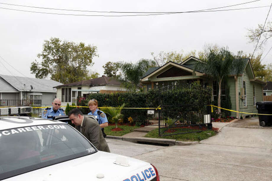 A detective talks with the spouse of the victim on Tuesday as members of the Houston Police Department's homicide team investigate an apparent home invasion at a residence in the 1300 block of East 34th Street. Photo: Todd Spoth, Chronicle