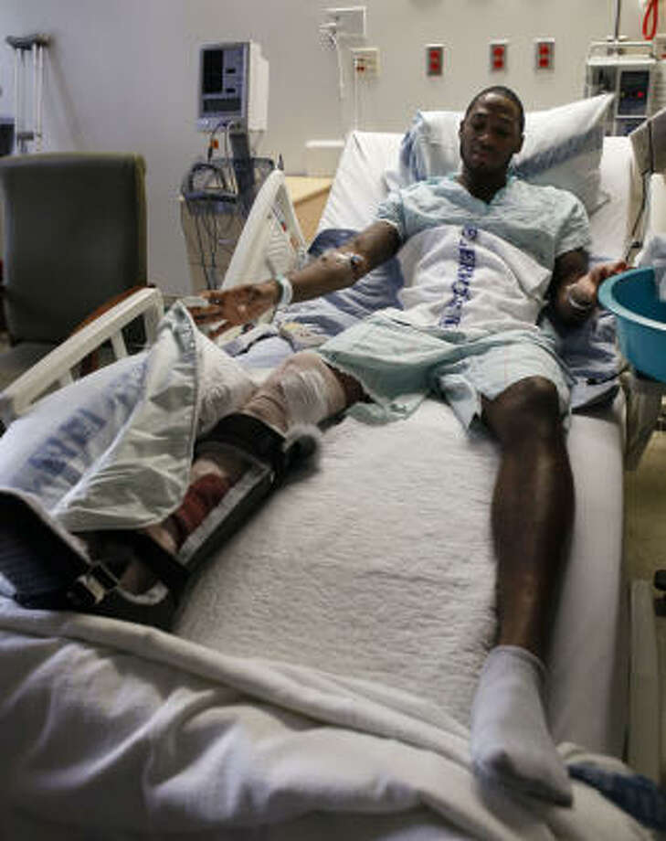 Texas A&M's Derrick Roland takes a look at his surgically-repaired right leg as he rests in a hospital bed following surgery. Photo: Elaine Thompson, AP