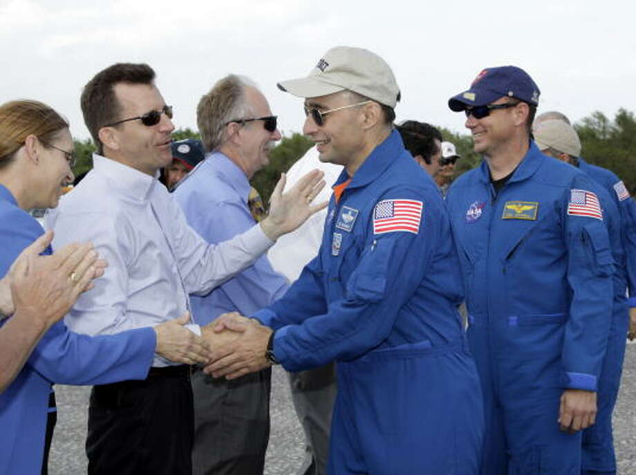NASA workers welcome back Discovery crew members Lee Archambault, second from right, and pilot Tony Antonelli at Kennedy Space Center. Photo: TERRY RENNA, AFP/Getty Images