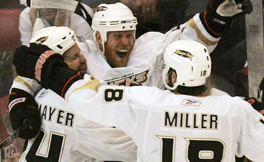 Ducks center Todd Marchant, center, celebrates his game-winning, third overtime goal with teammate wingers Rob Niedermayer (44) and Drew Miller (18). Photo: Andre Jackson, AP