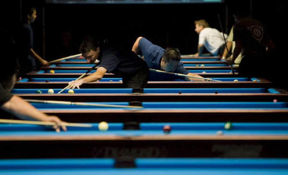 Players line up their shots on Thursday during The Galveston World Classic pool tournament at Moody Gardens. Photo: James Nielsen, Chronicle