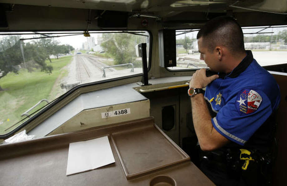 Seeing a car illegally stopped on the rails Tuesday, Katy police officer Tim Parnell radios from his post inside a train to units on the street to pull over the driver. Photo: Melissa Phillip, Chronicle
