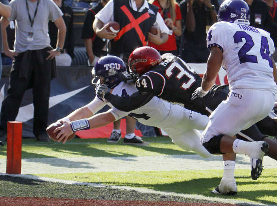 TCU quarterback Andy Dalton dives for the pylon while scoring on a 7-yard touchdown run with San Diego State linebacker Jerry Milling on his back during the second quarter. Photo: Lenny Ignelzi, AP