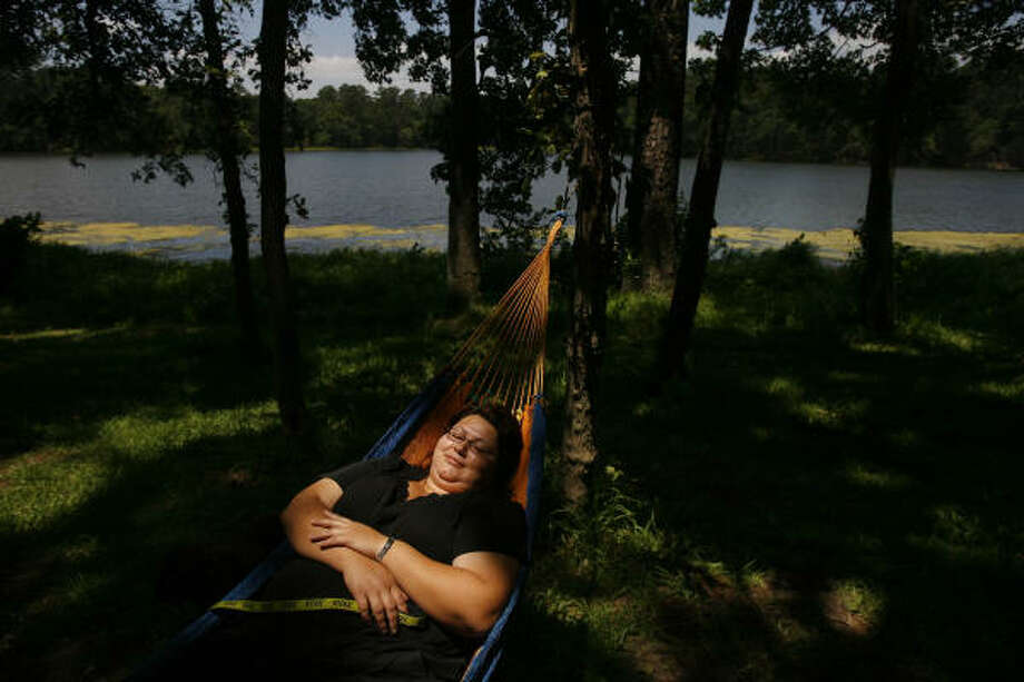 Martha Matas enjoys resting on her hammock near the lake at Huntsville State Park, which her family chose for their weekend vacation. The Matas family has a tradition of gathering at the state park at least once a year, and the inexpensive price makes it an even more attractive location. Photo: Mayra Beltran, Chronicle