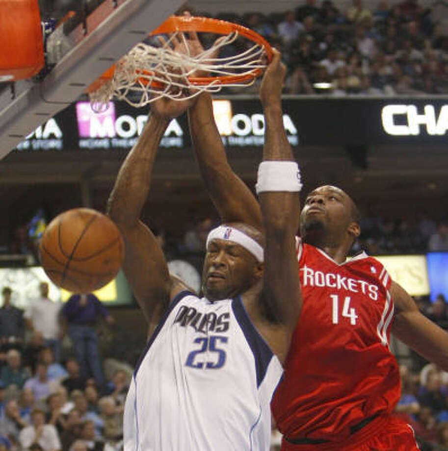 The Mavericks' Erick Dampier, left, dunks the ball as Rockets forward Carl Landry tries to defend. Photo: RICHARD W. RODRIGUEZ, MCT