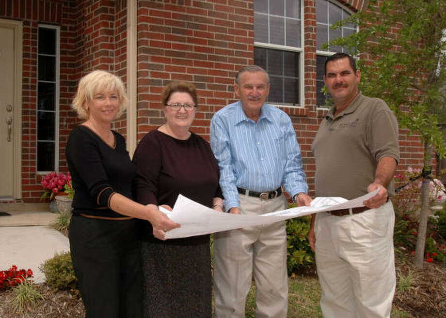READY TO MOVE IN: Bayway Homes sale counselor Eloise Cavey, left, stands with new townhome owners Barbara and Ed Grein, and Bayway Homes builder Scott Mixon, while looking over the floor plan of the Grein's new townhome. Photo: GEORGE WONG, For The Chronicle