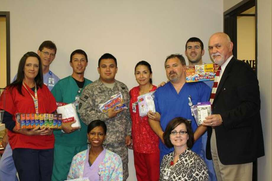 A SIGN OF THANKS: Members of the Imaging Department at HCA Affiliated Kingwood Medical Center show off some of their collected items. Standing are Stacy Lapaglia, left, Scott Rawls, Chris Baade, Army specialist Matthew Torres, Olga Caldas, Joe Pierce, Ryan Castille, and Jim Wall. Kneeling are Juanita Bowie  and Amber C. Corley.