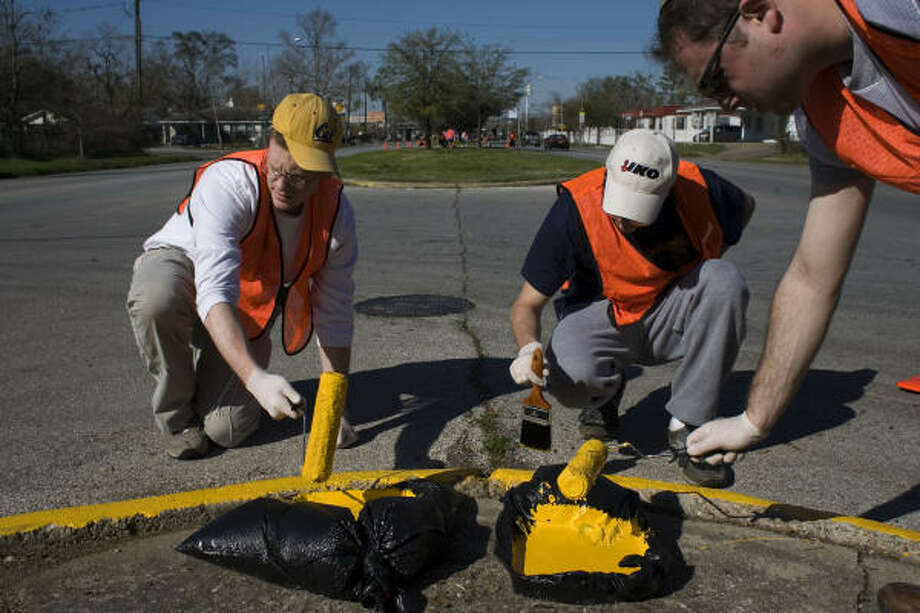 Volunteers Jason Allen, left, David Eckstein and Dov Goldstein — all from Yeshiva University in New York City — help paint median curbs along MLK Boulevard, south of Interstate 610, last week. Photo: Eric Kayne, Chronicle