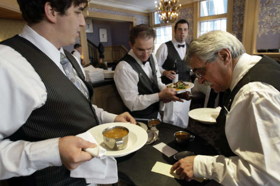 Waiters Will Lloyd, left, Odell Bryant, Edward Knight and Paul Tuzzo prepare to serve a table at Commander's Palace in the Garden District of New Orleans. Photo: ALEX BRANDON, ASSOCIATED PRESS