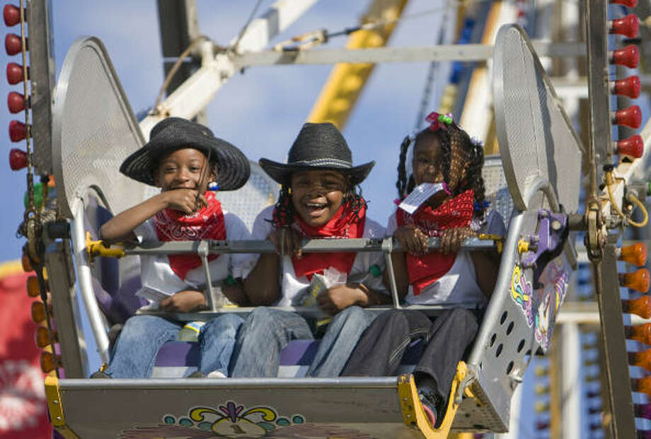 Azaria Jackson, 6, left, Jermaya Lott, 7, center, and Yasmyne Winston, 6, enjoy the ferris wheel in the Kids Country Carnival during the Houston Livestock Show and Rodeo on Thursday. The girls are participating in the Rodeo Institute for Teaching Excellence. Photo: Nick De La Torre, CHRONICLE