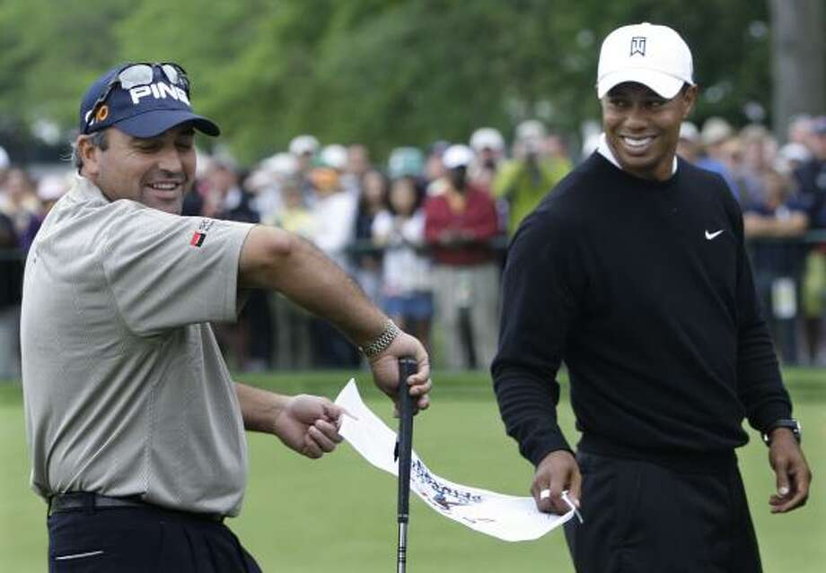 Angel Cabrera, left, and Tiger Woods share a lighter moment Tuesday before things get serious on Thursday, when the two will be joined by Padraig Harrington in a star-studded group. The threesome represents the reigning champions of the major events. Photo: Charles  Krupa, AP