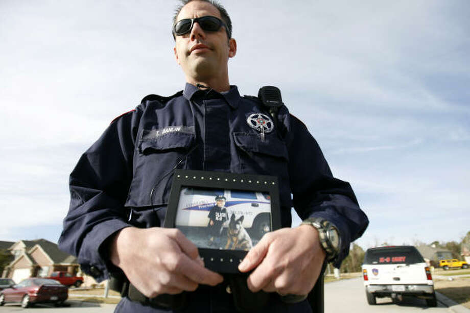 Ted Dahlin, a Harris County Pct. 4 deputy constable, holds a photo of his police dog, Blek, photographed with Dahlin's daughter, Emily. Blek was allegedly strangled by a burglary suspect in a wooded marsh in north Houston on Dec. 22. Photo: Karen Warren, Chronicle