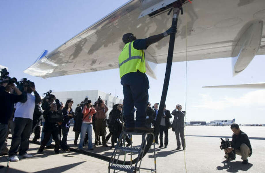 A Continental employee prepares to unhook a fuel hose at a news conference on the biofuels test flight of a Continental Airlines Boeing 737-800 jet. Photo: James Nielsen, Chronicle