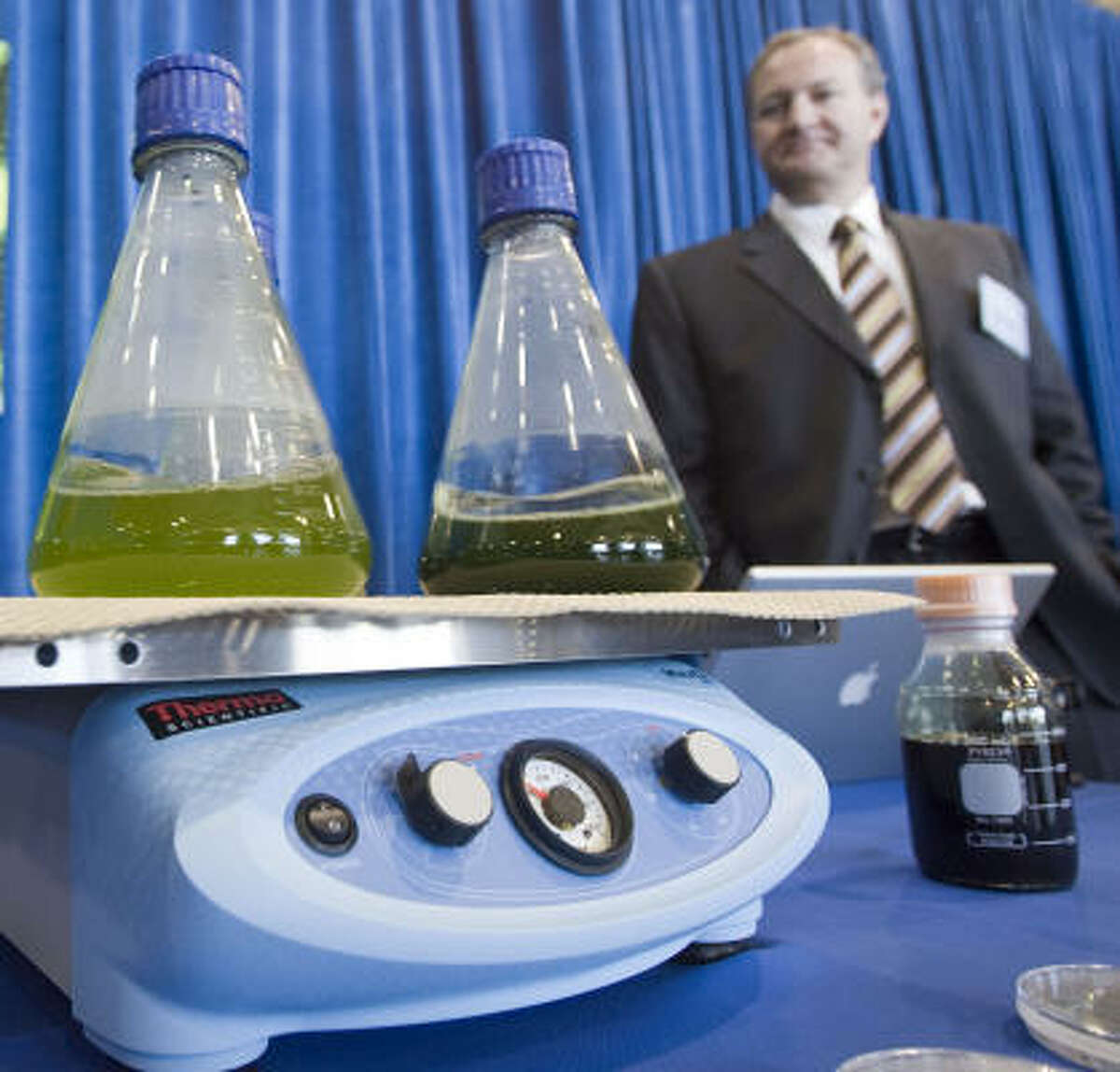 Sapphire Energy's Tim Zenk stands over Sapphire's booth, which illustrates the process of making biofuel from algae during a news conference on the first flight of a Continental Airlines Boeing 737-800 jet aircraft running partially on biofuel on Wednesday.