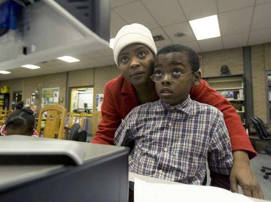 Judith Theodore helps her son Steven, 11, with homework at a public library in Washington, D.C. The unemployed real estate agent says her monthly $1,100 budget won't cover broadband service. Photo: Washington Post