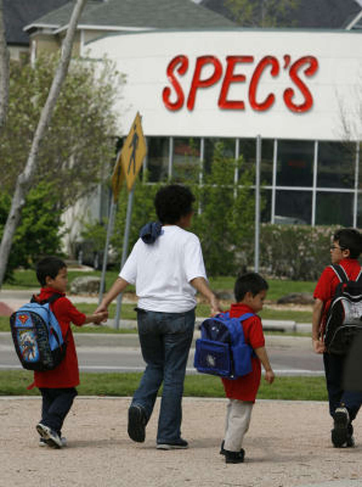 A woman walks children home from school across the street from the new Spec's location at the traffic circle at Washington and Westcott.