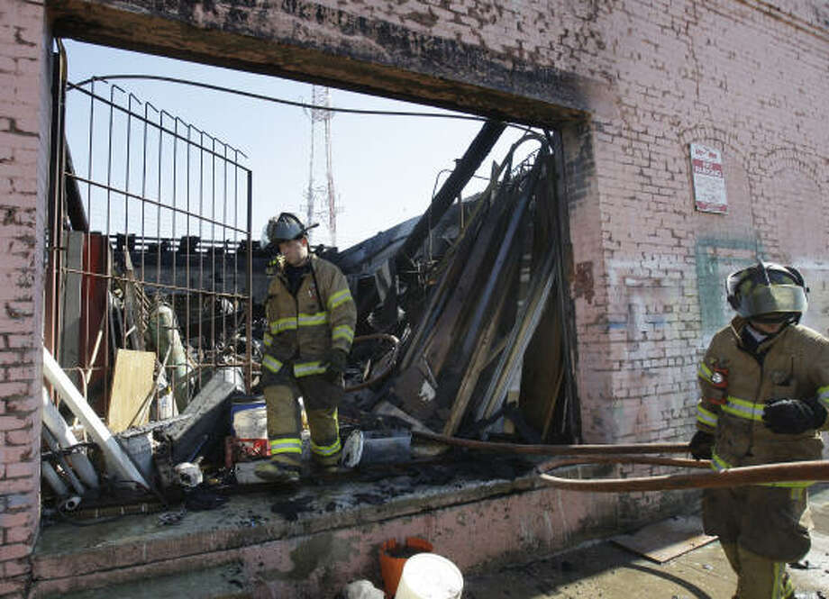 Galveston firefighters clean up after a fire that damaged a contractor's warehouse on Tuesday. No injuries were reported. Photo: Melissa Phillip, Chronicle