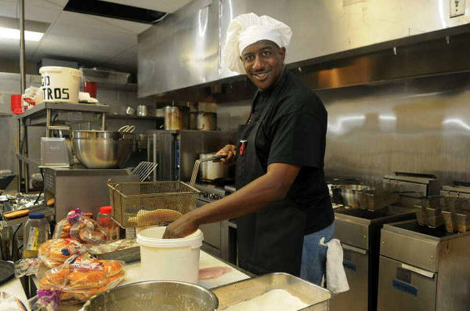 Former Harlem Globetrotter Paul Gaffney works in the kitchen at the southern cuisine restaurant Vivian's, which he opened in Magnolia. Photo: Jerry Baker, For The Chronicle