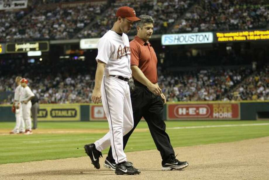 Astros starter Roy Oswalt leaves the game with trainer Nathan Lucero after experiencing tightness in his lower back during the seventh inning. Photo: David J. Phillip, AP