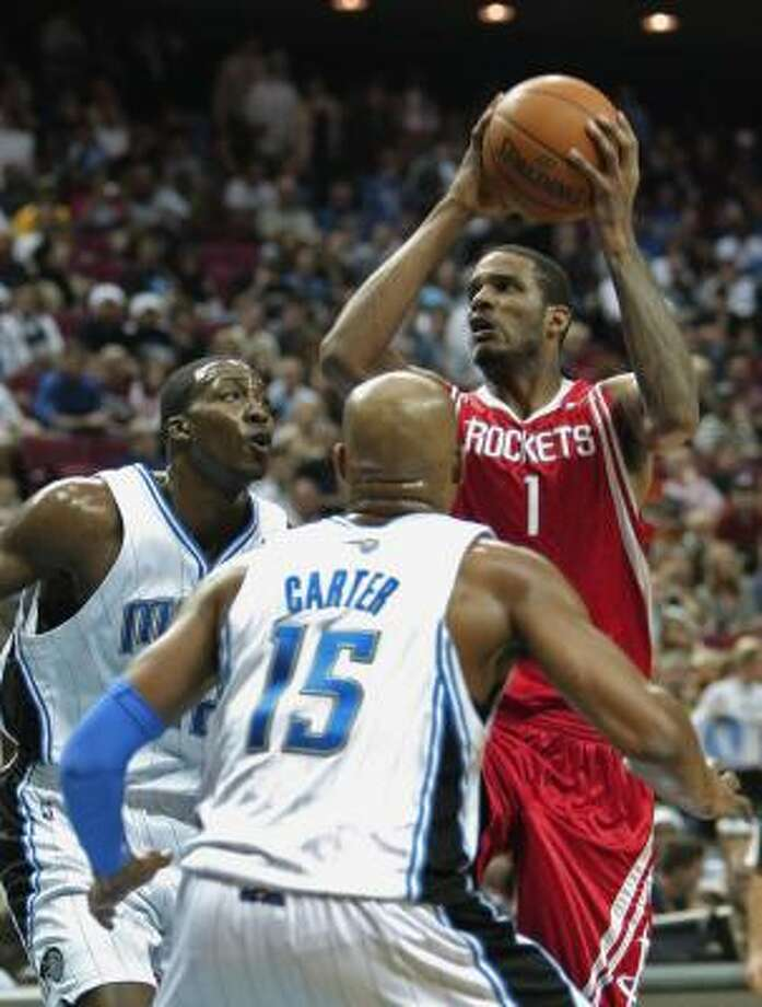 Rockets forward Trevor Ariza takes a shot over Magic center Dwight Howard, left, and guard Vince Carter during the first half. Photo: John Raoux, AP