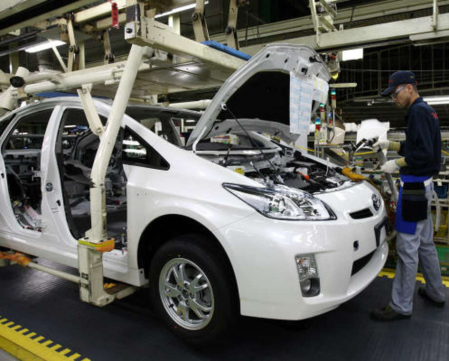 A worker assembles a Prius at Toyota City, Japan. The popularity of such cars is a drain on government tax revenue. Photo: TOMOHIRO OHSUMI, BLOOMBERG NEWS