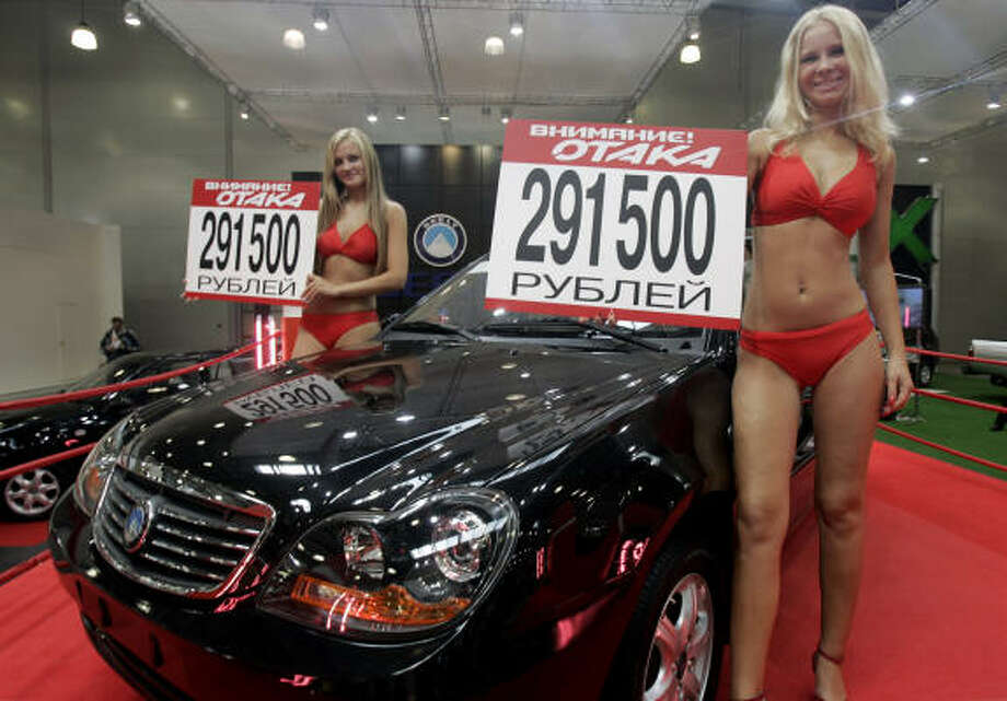 """Models advertise the Geely Otaka, a car designed in China, during a 2007 auto show in Moscow. The signs read """"Attention! Otaka — 291,500 rubles (then, $11,300)."""" Photo: Ivan Sekretarev, Associated Press File"""