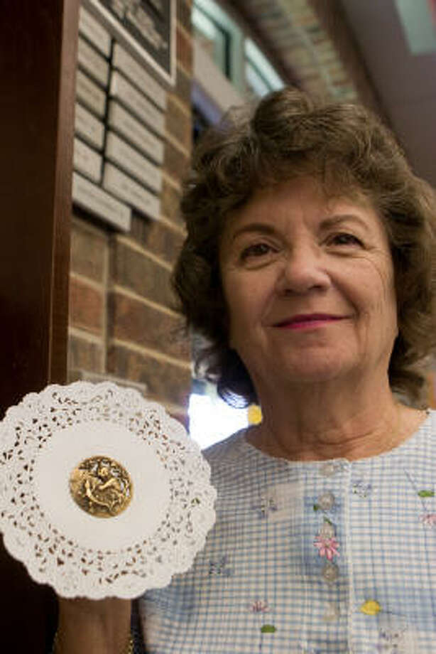 Jeannette Faris shows one of her more unusual buttons, a cat chasing a lizard. Photo: R. Clayton McKee, For The Chronicle