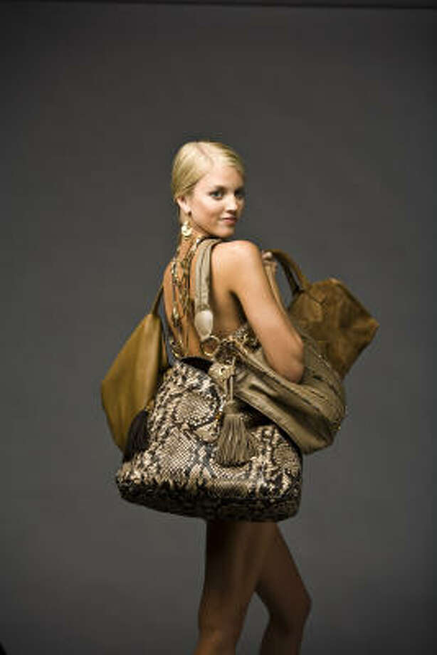 """Lauren Ufer of Page Parkes Models carries bags for fall: From left: Valentino's large 360 bag in brown nappa, $1,395, Valentino boutique; Gucci's anaconda bag, $5,700, Saks Fifth Avenue; Lenny e Cia's beaver and python drawstring bag, $3,300, Lenny e Cia; Yves Saint Laurent's small """"Easy"""" bag in embossed tan lizard, $995, www.saks.com; and Fendi's """"Peekaboo"""" bag, $3,940, Neiman Marcus. Styling by Wendy Norwood Patterson of the Neal Hamil Agency; hair and makeup by Kathy White of Pastorini-Bosby Talent. Photo: Nick De La Torre, Chronicle"""