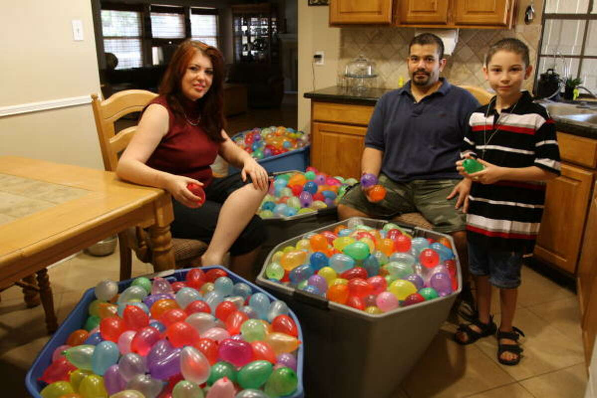 Marco and Kim Cerda run a water-balloon business out of their home in west Houston. From left are Kim, Marco and Marco, 8.