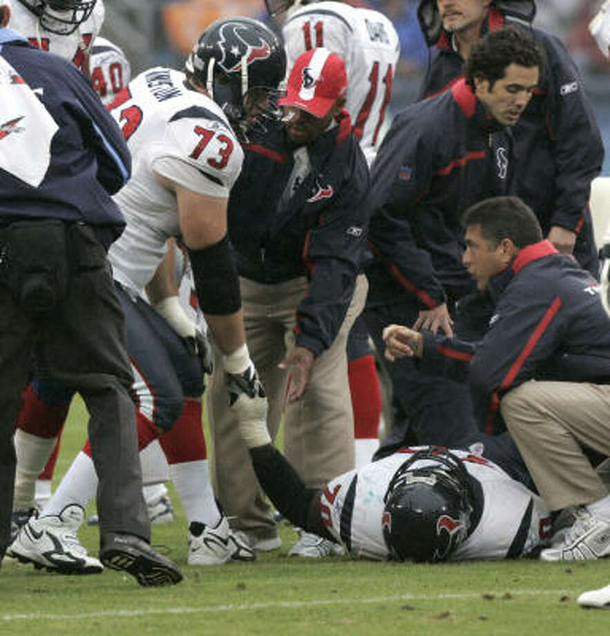 Houston Texans tackle Eric Winston (73) grabs Fred Weary's hand after Weary was injured against the Titans. Photo: Brett Coomer, Houston Chronicle