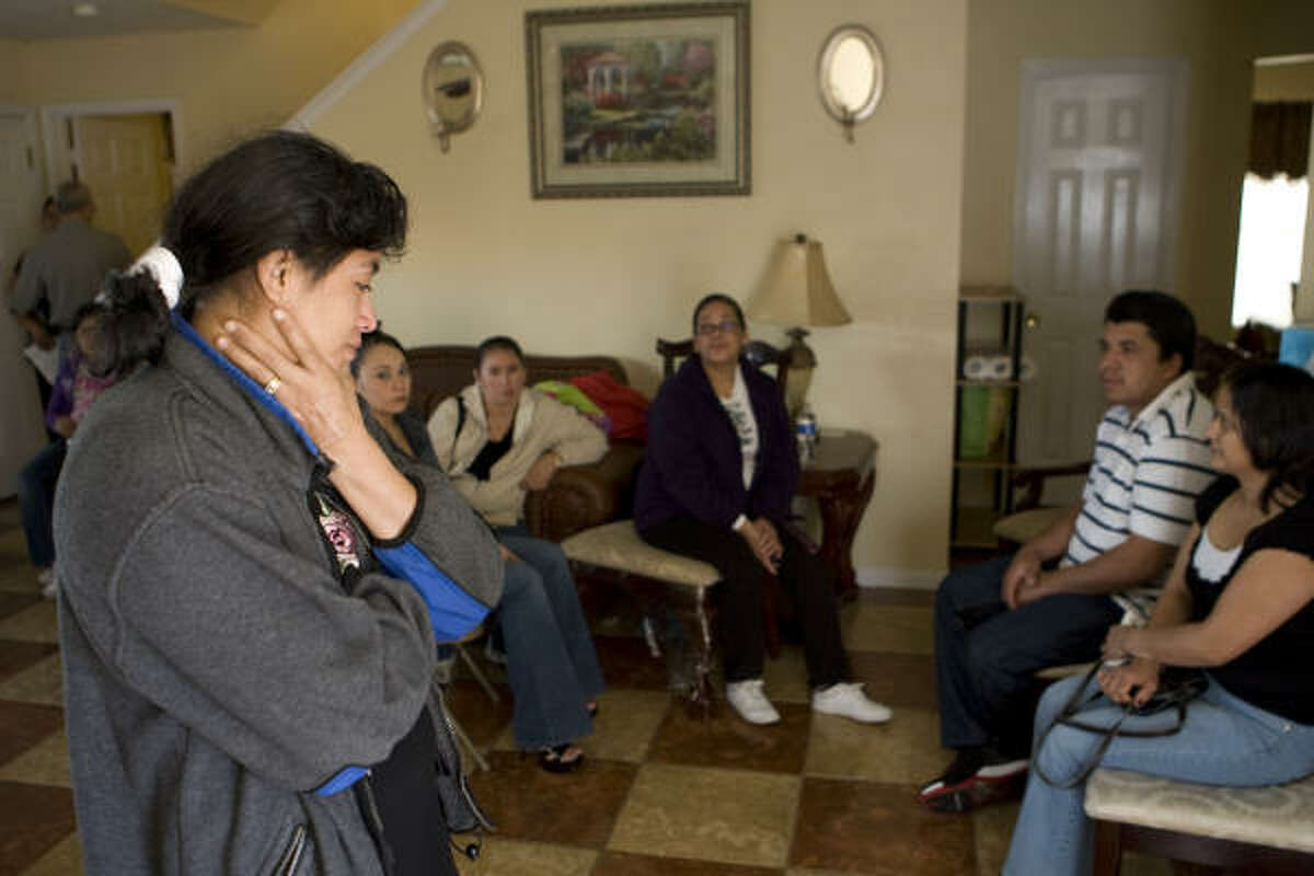 Ana Benson stands in her sister's living room with family as they mourn the loss of her brother-in-law, Jony Ventura, and his daughter Gabriela on Sunday.