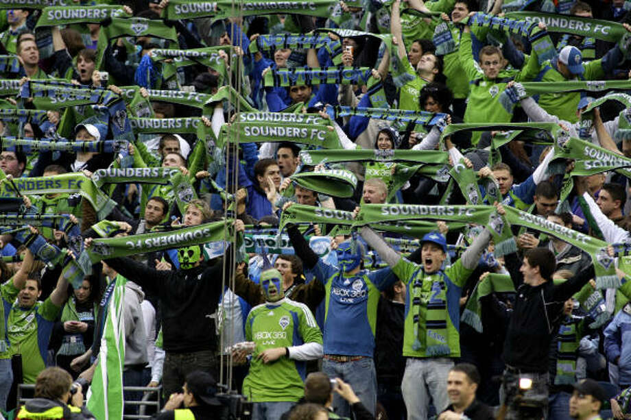 Seattle fans lift their scarves to salute their new MLS team. More than 32,000 were at the season opener. Photo: Ted S. Warren, AP