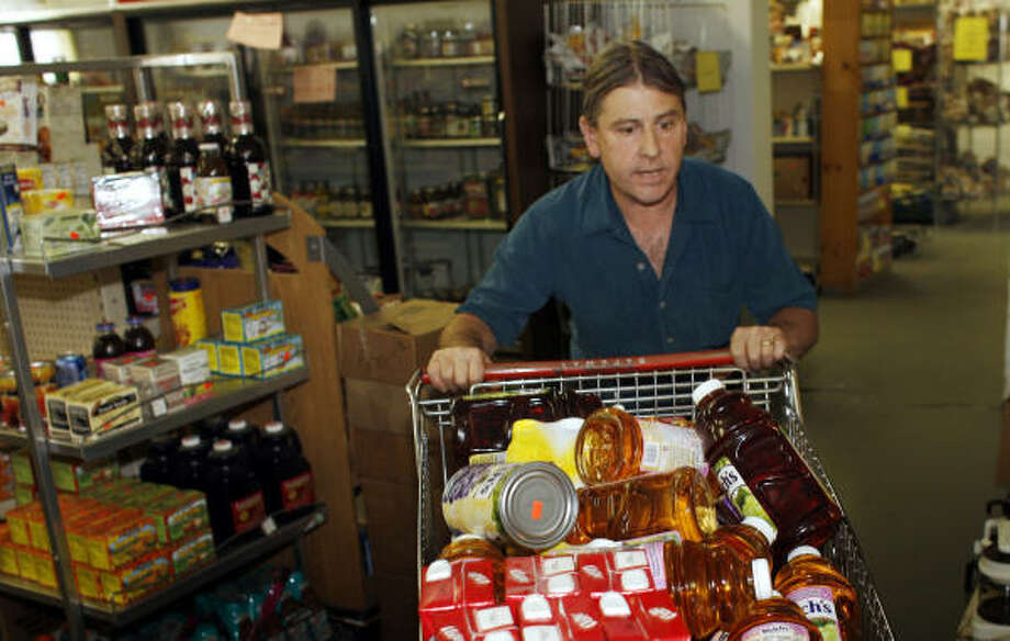 Friday Store co-owner Martin Palumbo wheels a cart filled with goods in Arvada, Colo. Palumbo said he has had to raise prices, but tries to keep them lower than bigger grocery stores. Photo: David Zalubowski, AP