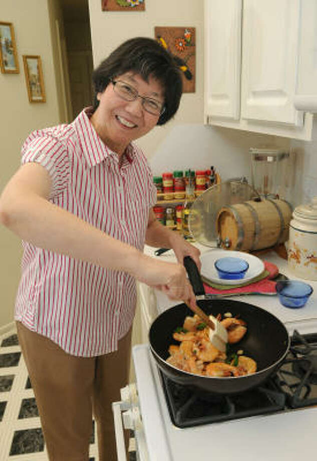 Yabin Yu, 64, prepares her Sauteed Shrimp with Green Peas, one of the recipes in her recently created cookbook, The Bear and Fish Family Cookbook, in the kitchen of her The Woodlands home. Photo: Jerry Baker, For The Chronicle