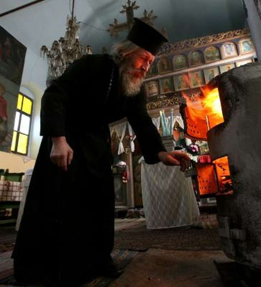 A Bulgarian priest fires up a wood-burning stove at church. A fight between Russia and Ukraine over fuel has hurt Europeans. Photo: PETAR PETROV, ASSOCIATED PRESS