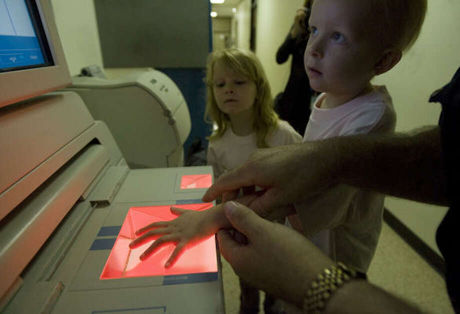 With sister Bailey, left, watching every move, 5-year-old Delaney Starcher learns firsthand about fingerprints Saturday while touring the Harris County Sheriff's Office, 1301 Franklin. Photo: James Nielsen, Chronicle
